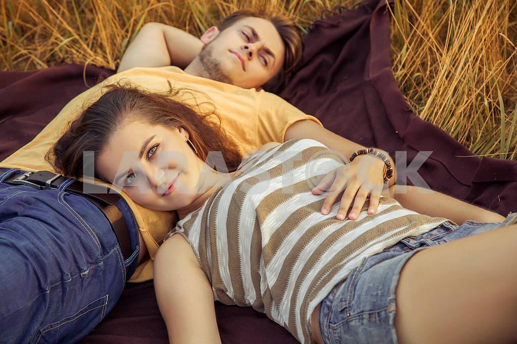 Young fashion beautiful loving casual style couple  lying down on floral field in autumnal park, warm sunny day, enjoying family, romantic date, happiness and love concept. — Image 19847