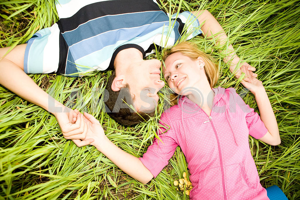 Young love couple lay on green grass outdoors — Image 6757