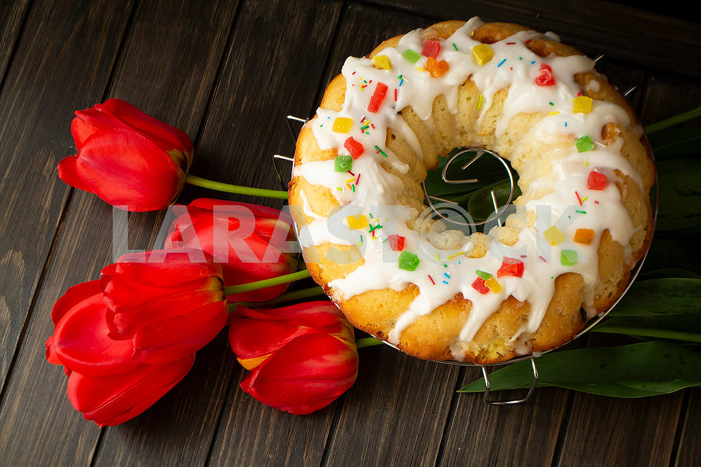 Walnut brioche roll or babka on dark wooden table with red tulips — Image 83057
