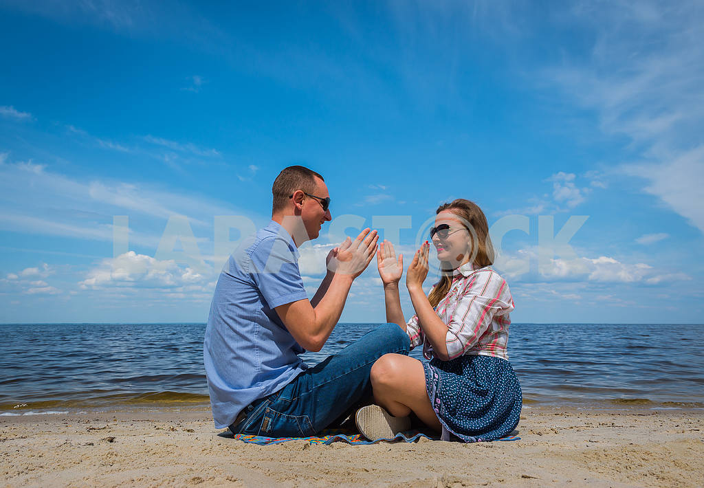 A loving couple sittingon the beach, near the water, playing with each other, blue sky on the background, sunny day, wide angle, long white clouds — Image 37977