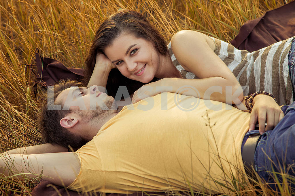 Young fashion beautiful loving casual style couple  lying down on floral field in autumnal park, warm sunny day, enjoying family, romantic date, happiness and love concept. — Image 19838