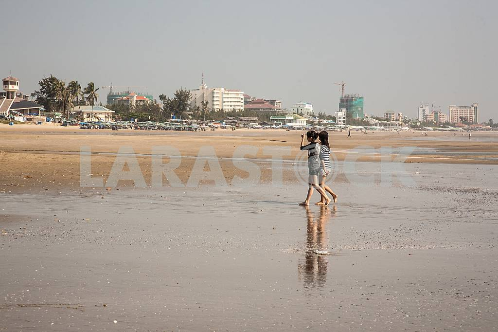 Two girls walk barefoot on the beach — Image 28138