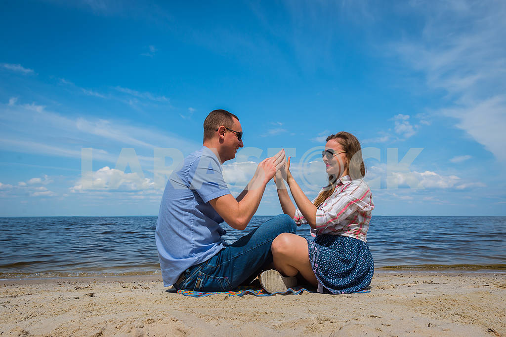 A loving couple sittingon the beach, near the water, playing with each other, blue sky on the background, sunny day, wide angle, long white clouds — Image 37978
