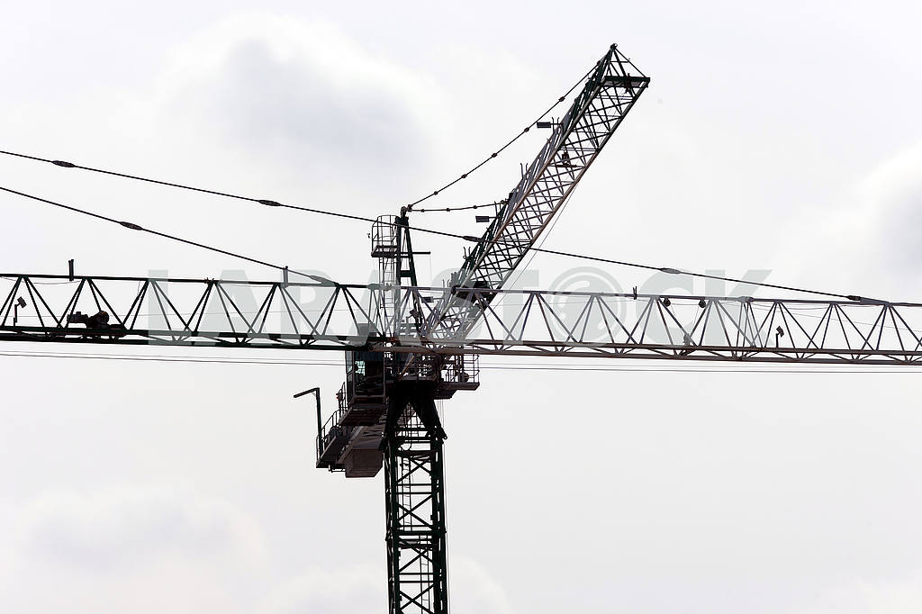 Silhouettes of cranes with a load on the construction of buildin — Image 49978