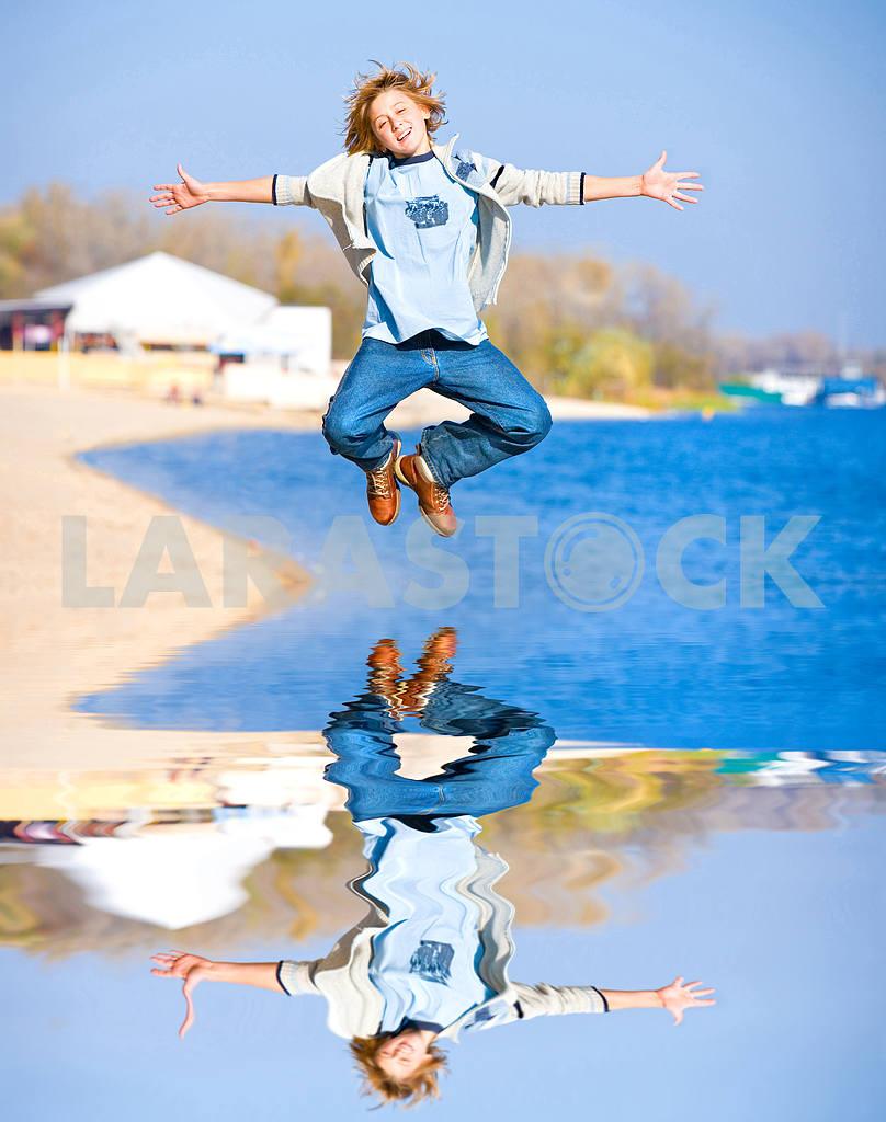 Счастливый прыжков мальчик на пляже — Изображение 8988