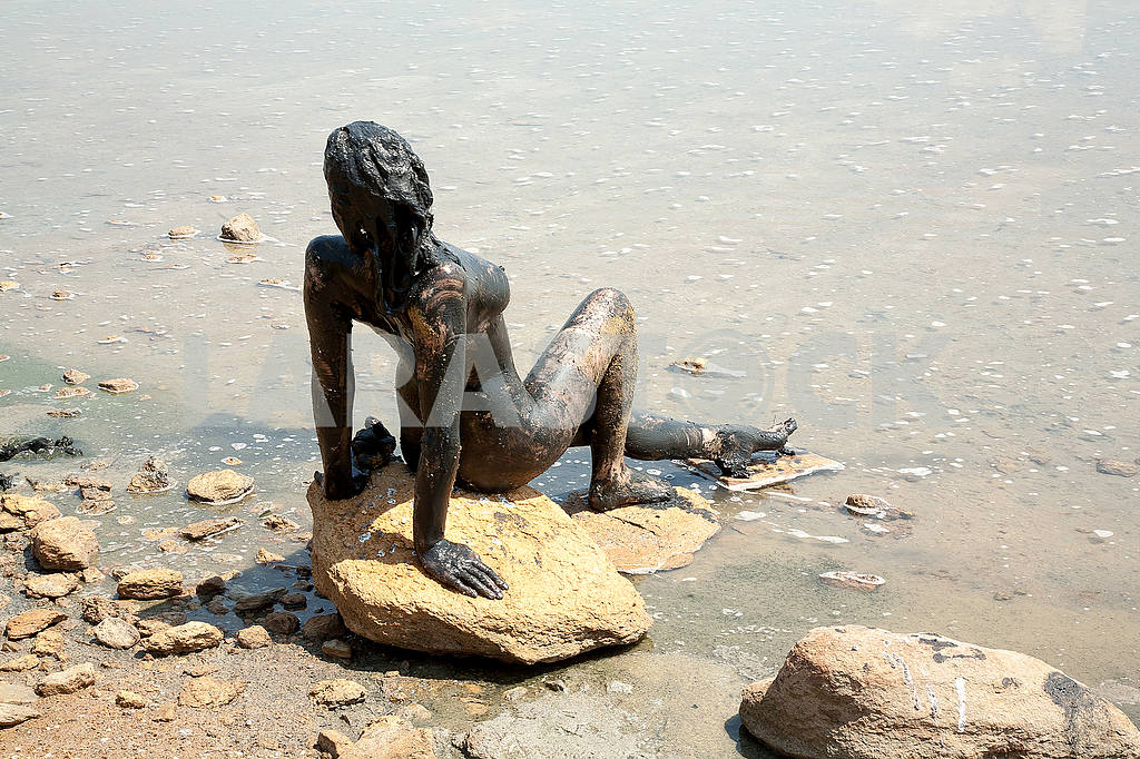 A girl sitting on a stone near the lake, smeared with mud — Image 50198