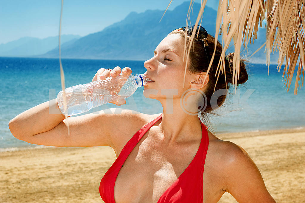 Beautiful girl drinking water against blue sea — Image 6519