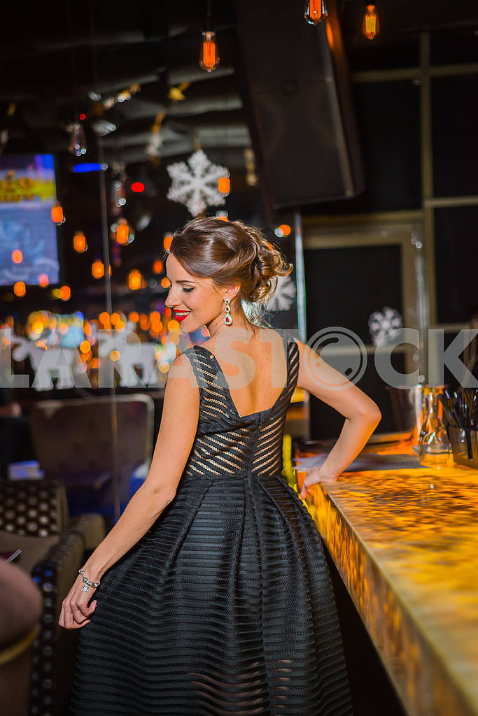 Beautiful brunette woman walking out in the restaurant, in black dress and red shoes. Smiling with her red lips, shy like a little girl showing her back — Image 37629