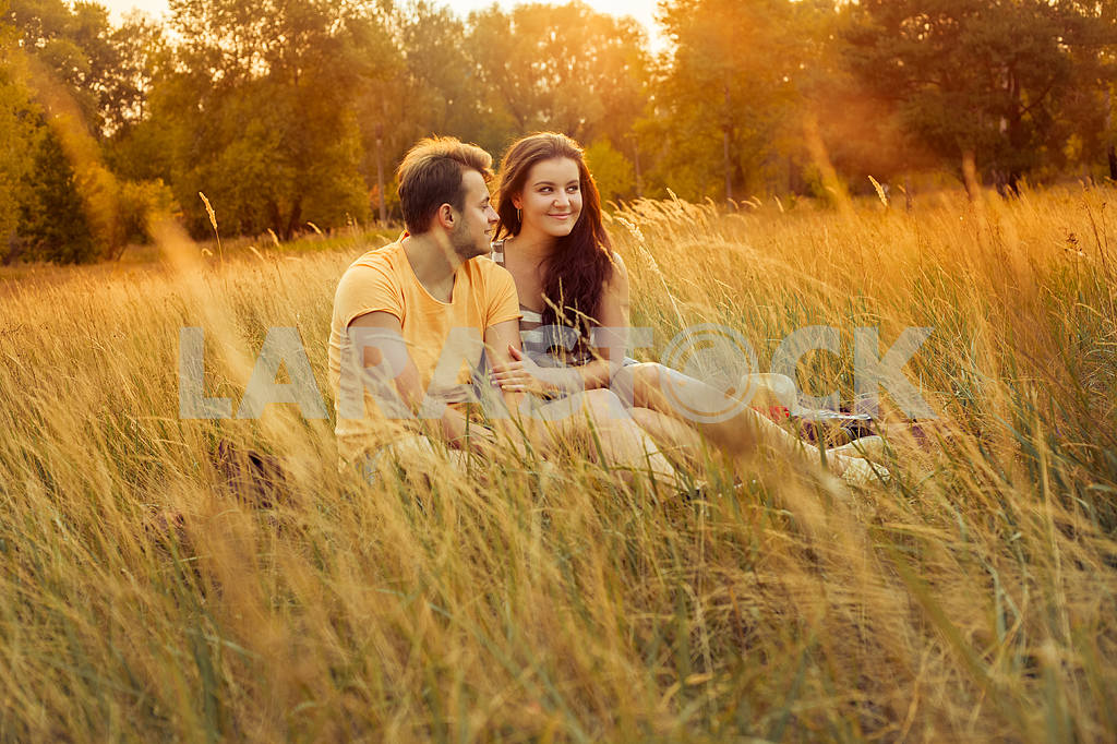 Young fashion beautiful loving casual style couple  lying down on floral field in autumnal park, warm sunny day, enjoying family, romantic date, happiness and love concept. — Image 19849