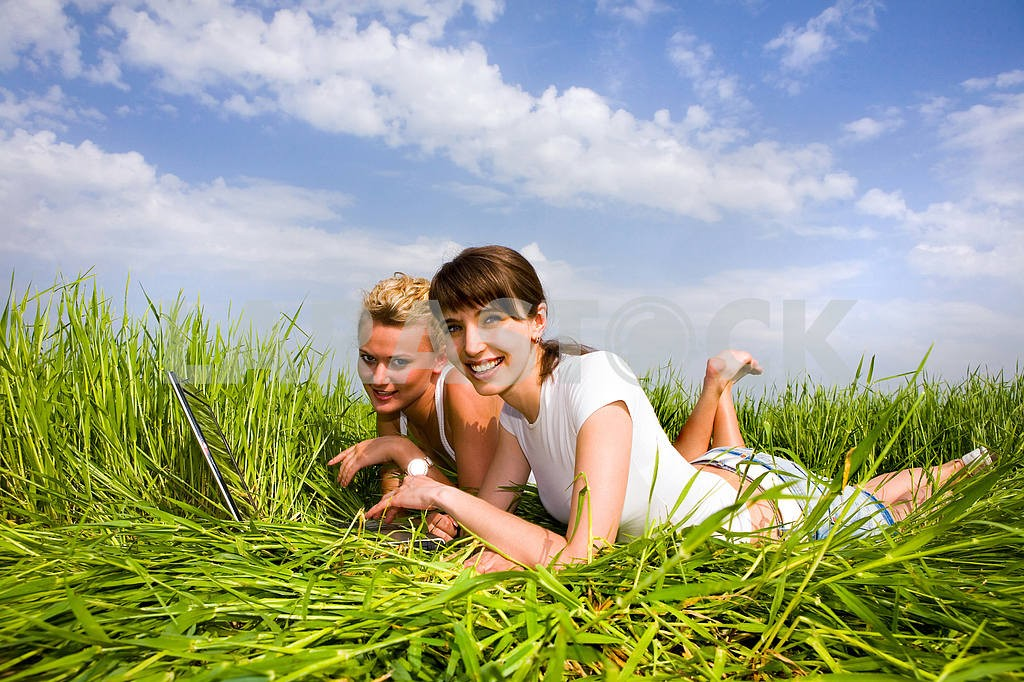 Two beautiful girls in white clothes are laughing near laptop co — Image 9299
