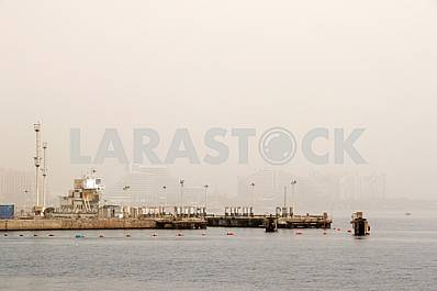 Pier with the misty shore of Eilat on background