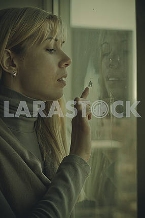 Young girl sitting by the window draws heart
