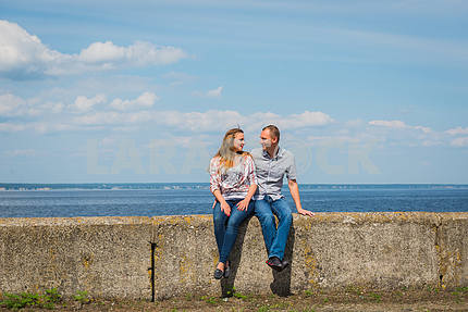 Couple in love embracing, sitting together, holding with the hands, near the water on a sunny day, blue sky with long white clouds on the background. men and women are  smiling, looking on each other