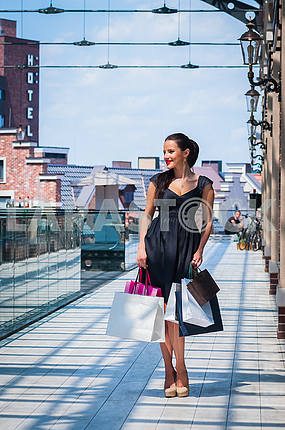 A young beautiful brunette woman going for shopping, among the Street Shopping Centre, in black dress with packages in her hand, happy smiling