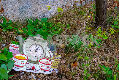 Old wall clock lie on the street on the grass.