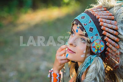 Indian woman outdoors at sunset. native american style. Background with free text space Young woman dressed in an Indian style in the woods Portrait of a young lady in the Indian roach