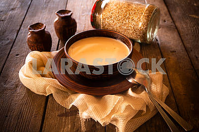 Boiled buckwheat with milk in wooden bowl on rustic wooden background