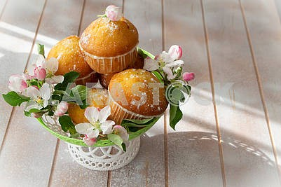 Small freshly muffins in lace wicher basquet and spring flowers, copy space