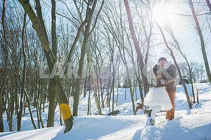 Wedding couple in a showy wither day, kissing, in the forest. rustic style  short wedding dress. Girl brunette. beautiful bride. bright sun lights.