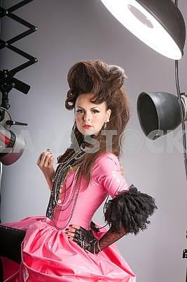 Brunette in red dress posing in photo studio