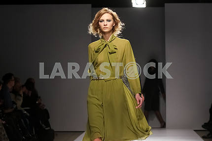 A model in an olive dress. Display by V by Gres