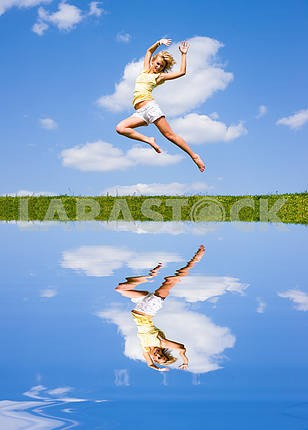 Happy young woman is jumping. Reflected in water.