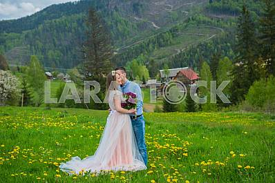 Wedding in mountains, a couple in love, mountains background, standing surrounded dandelions, among the lawn with the green grass, rustic style, girl in long tulle dress, romantic landscape, kissing