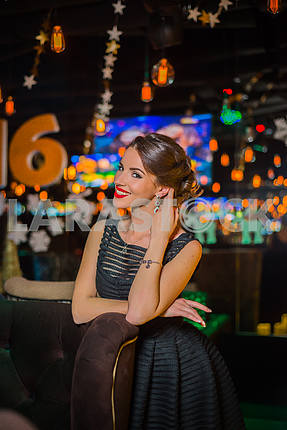 Beautiful brunette woman portrait in the restaurant, in black dress and red shoes. Smiling with her red lips