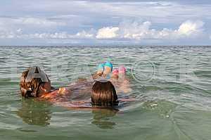 Two girls are sailing on the waves back. Zanzibar