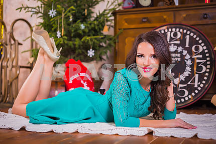 Beautiful brunette woman lying on the floor among the new years decorations in bright blue dress, smiling