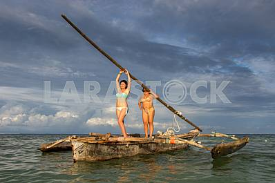 Two girls hold the mast.