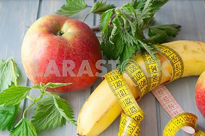 Vitamin fitness diet, red apple, nettle and banana with a centimeter tape.