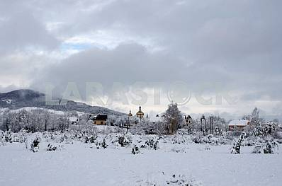 Winter landscape. Snow-covered village with houses and a church in the background of the mountains.