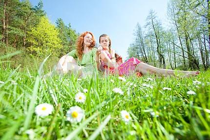смешно мать и дочь , сидя на зеленой траве