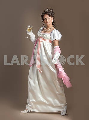 Girl in old fashioned dress with a glass of champagne