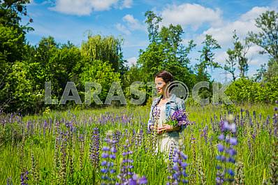 Young woman, happy, standing among the field of violet lupines, purple flowers. Blue sky on the background. Summer, sunny day!