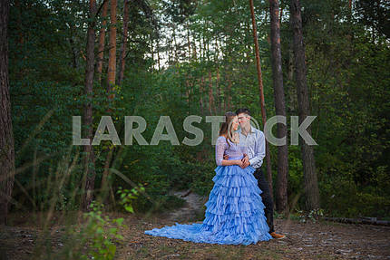 A love story couple, in love, together in the forrest park, girl in a beautiful violet dress,  evening, summer, holding each other, near the pine tree