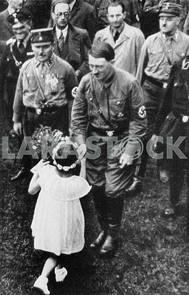 Girl gives flowers to Adulf Hitler.