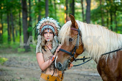 Beautiful girl in a suit of the American Indian woman in the roach with the horse