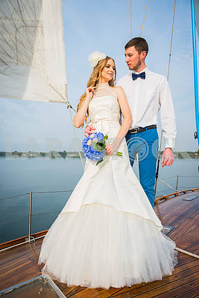 Happy bride and groom hugging on a sailing yacht with the blue bouquet in her hands on a sunny day; stylish, long dress, bow tie