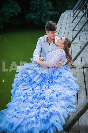 A love story couple, in love, together in the forrest park, on the wooden bridge, girl in a beautiful violet dress, sunny evening, summer, green water on the background