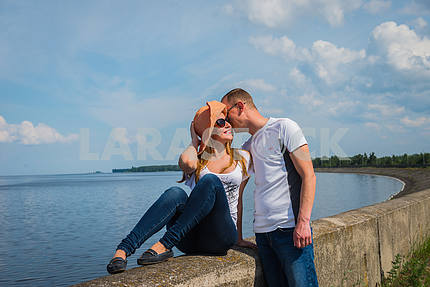 a love story couple traveling, resting near the water, looking into each other, on the sunny day, weared on jeans, blue sky and white clouds on the background, boy is telling something on her ear