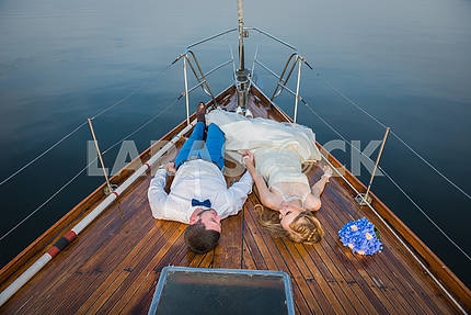 happy honeymoon sailing - Stylish young bride and groom laying on the wooden board the sailing yacht looking into each other