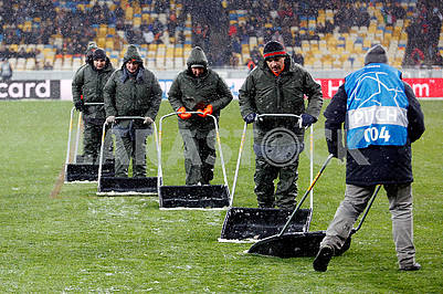 Stadium workers are clearing snow from the field