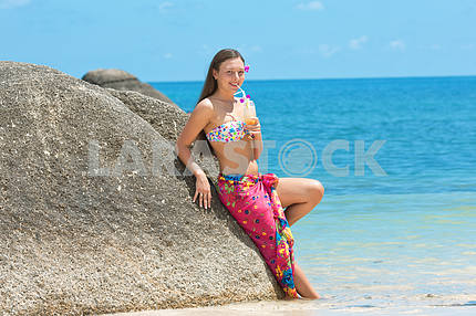 Beautiful young girl with a cocktail in hand on beach