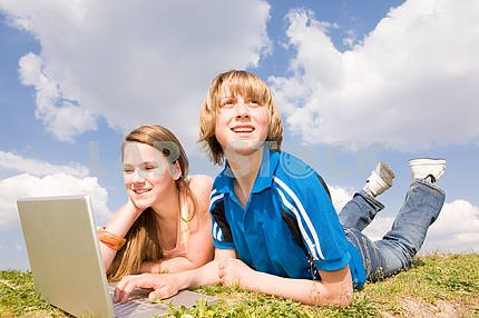 Two Smiling teenagers with laptop resting on meadow