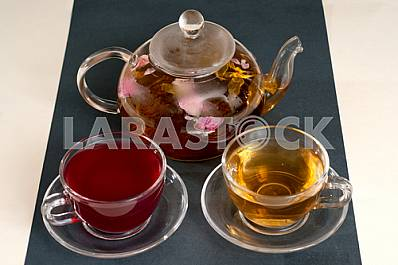 Flowering tea in clear glass teapot with teacups