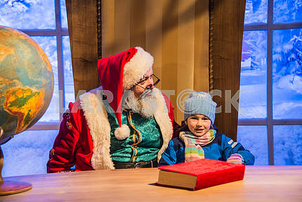 Santa Claus sitting in a chair with a girl in his arms