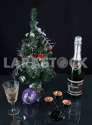 Christmas tree, champagne, glass and candles