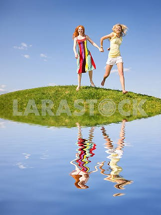 Two happy girls fleeing on a meadow. Reflected in water